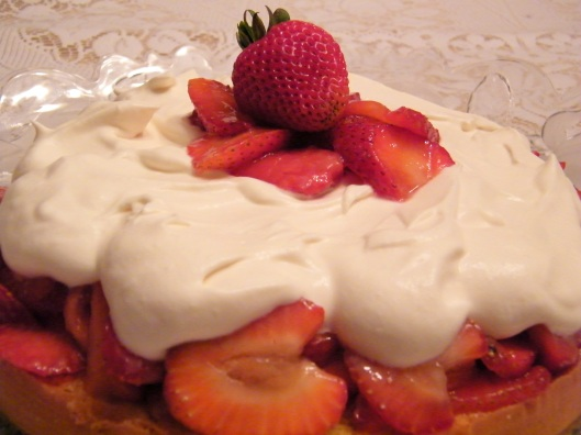 Strawberries and cream piled atop a not-so-tall cake.
